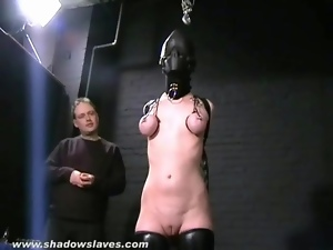 Hooded girl takes painful tit torture