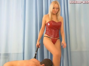 Mistress in red latex corset abuses him