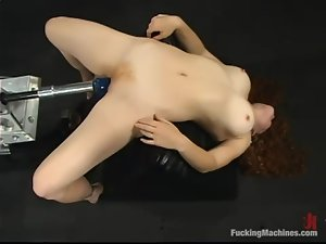 Redhead cutie Randi moans sweetly while being fucked by a sex machine