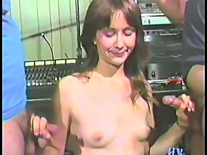 Shy slim brunette enjoys sucking two dicks in a vintage clip