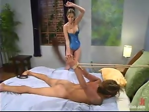 Sexy mistress in a corset humiliates her sex slave in a bedroom