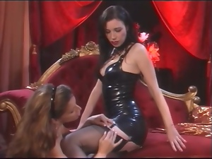 Brunette in leather dress gets her feet licked by another girl