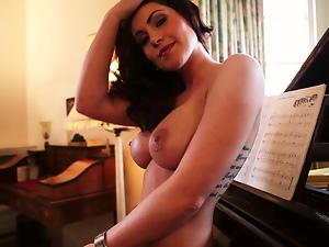 Busty Amber Price poses naked by the grand piano