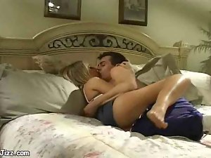 Blonde woman fucks guy on a big soft bed