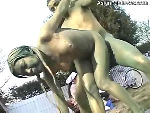 A couple poses as statues as they fuck in the park