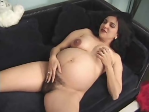 Sexy pregnant brunette enjoys toying her hairy cunt indoors