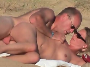 French couple bang in side-by-side position on a beach