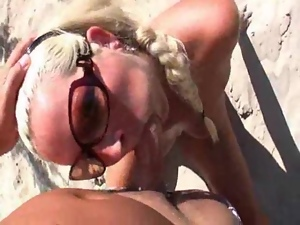 German blonde sucks a dick on a beach and enjoys doggy style sex