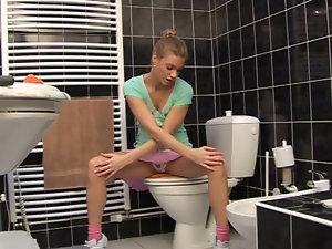 Megan is pleasing herself in the bathroom