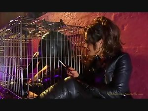Dominatrix Anabelle forces her caged slave to breathe her smoke.
