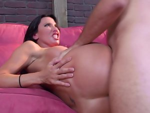 Mega boobs bimbo is getting penetrated on the sofa by a man