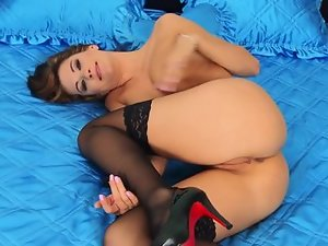 A brunette sticks a dildo in her pussy and she moans loudly when it happens