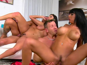 Two girls are licking two large peckers in a foursome