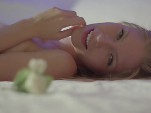 A fit pale blonde sits alone on the bed with a smile on her face