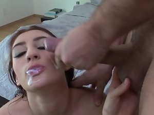 A girl with nice tits is handling a large dick with her hands